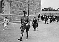 Michael Collins strides through Cathal Brugha Barracks, Dublin. A young civilian piper, Alphonsus Culloten, follows in tow. The shot was taken on Collins' return from a memorial service on the 7 August, 1922. Just over two weeks later, he was shot dead by anti-Treaty forces in Cork. (Part of the Independent Newspapers Ireland/NLI Collection)