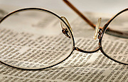 Eyeglasses and a newspaper rest on a table.