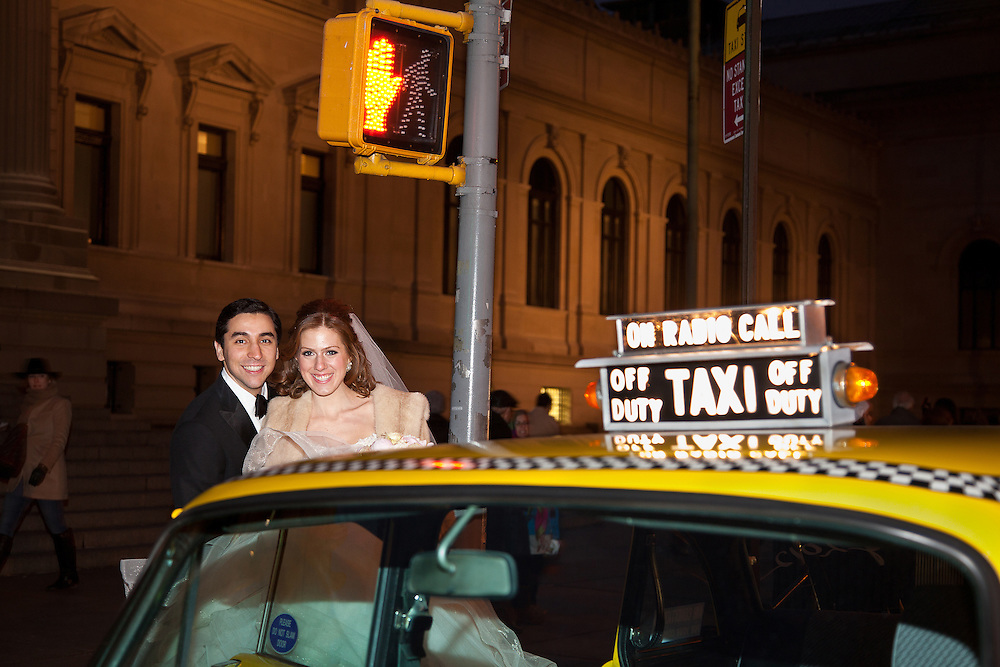 Bride and groom pose with classic NYC taxicab at night