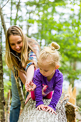 A woman shows a dragonfly to a young girl in the woods at the Orris Falls Preserve in South Berwick, Maine.