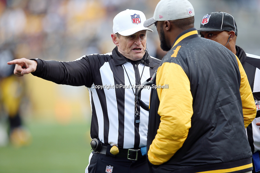 Referee Ed Hochuli (85) points and talks to Pittsburgh Steelers head coach Mike Tomlin on the sideline during the 2015 NFL week 6 regular season football game against the Arizona Cardinals on Sunday, Oct. 18, 2015 in Pittsburgh. The Steelers won the game 25-13. (©Paul Anthony Spinelli)