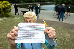 """© Licensed to London News Pictures. 16/05/2020. Manchester, UK. A woman holds up a leaflet with anti 5G rhetoric printed on it . An anti-lockdown, """"mass gathering"""" demonstration is held in Platt Fields Park in protest at government measures to control the spread of Covid-19. A group calling itself the UK Freedom Movement has organised a series of demonstrations across the UK. Photo credit: Joel Goodman/LNP"""