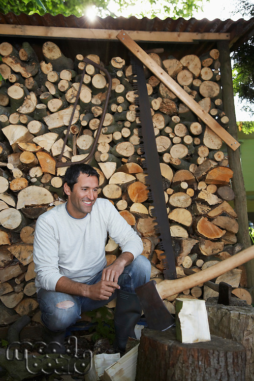 Man crouching beside axe at timber shed
