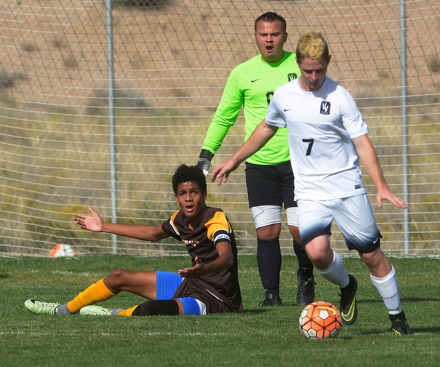 gbs092816o/SPORTS -- Cibola's Benjamin Rogers, left,  expects a referee call after a fall at the Volcano Vista goal as Volcano Vista's goal keeper Jacob Mink, center, and Tyler Cole, 7, continue play during the game at Volcano Vista on Wednesday, September 28, 2016. (Greg Sorber/Albuquerque Journal)