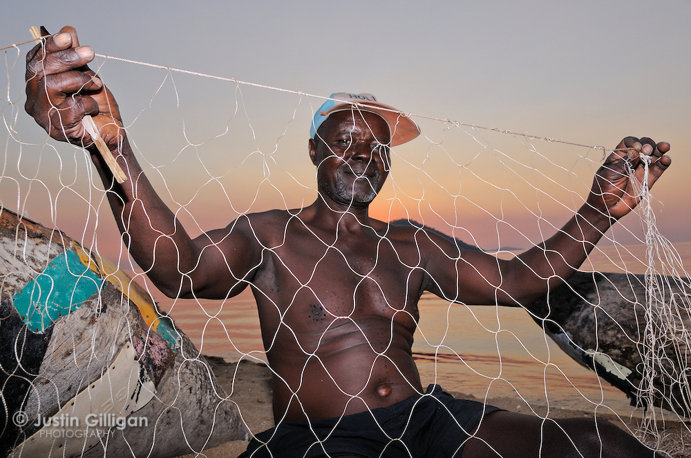 James Angry repairs fishing net on the shore of Cape Maclear, Lake Malawi, Malawi.
