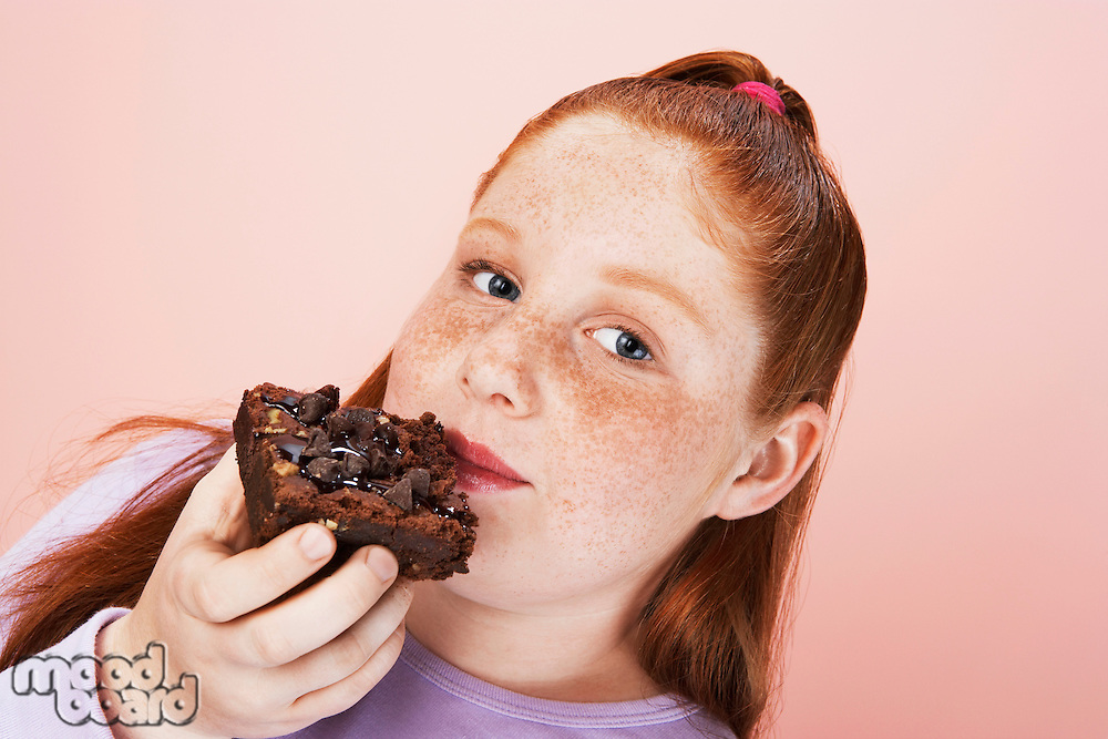 Overweight girl (13-15) Eating brownie portrait close-up