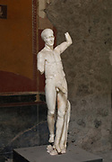 Statue of Priapus, god of fertility, with erect phallus, originally a fountain statue, found in the kitchen of the House of the Vettii, one of the largest houses in Pompeii, in the Parco Archeologico di Pompei, or Archaeological Park of Pompeii, Campania, Italy. Pompeii was a Roman city which was buried in ash after the eruption of Vesuvius in 79 AD. The site is listed as a UNESCO World Heritage Site. Picture by Manuel Cohen