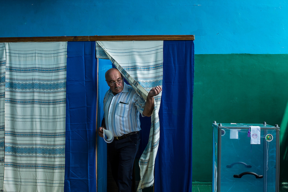 ULYANOVKA, UKRAINE - MAY 25: A man at a polling station emerges from a voting booth after filling out his ballot in Ukraine's presidential election on May 25, 2014 in Ulyanovka, Ukraine. The elections are widely viewed as crucial to taming instability in the eastern part of the country. (Photo by Brendan Hoffman/Getty Images) *** Local Caption ***
