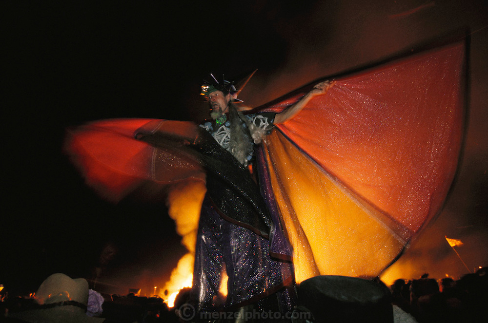 At the grand finale of the Burning Man festival, a man on stilts dressed like a wizard urges on the crowd, which had been held back by fire marshals and Burning Man Rangers until the Burning Man was mostly burned and the fireworks exploded. The crowd pushes forward to circle the burning man and begin a full night of revelry and dancing and more. Burning Man is a performance art festival known for art, drugs and sex. It takes place annually in the Black Rock Desert near Gerlach, Nevada, USA.