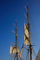 A view of two masts against the blue sky.