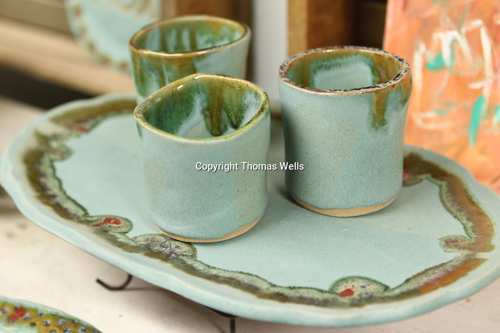 """A finished set of """"ocean"""" galzed pottery wais to be sold. You can see at the bottom of cups where the wax kept the colored glaze off the bottom of the cups."""