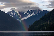 A Rainbow over Chilliwack Lake with Mount Redoubt in the background.  Photographed from the beach at Chilliwack Lake Provincial Park in Chilliwack, British Columbia, Canada. Mount Redoubt itself is in North Cascades National Park in Washington State, USA.
