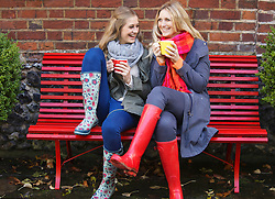 Mother and Daughter Sitting on Red Bench with Hot Drinks
