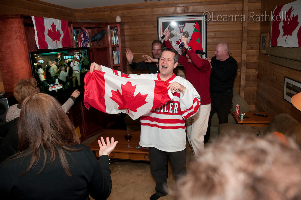 Friends gather at a house to watch the Canadians win gold in the final game of the 2010 Olympic Winter Games in Whistler, BC Canada.