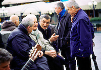 Italian men gathering and talking in Piazza Republica in Florence, Italy.