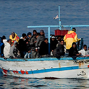 An Illegal boat transporting nearly 140 immigrants approaches the Island of Lampedusa. Despite the efforts of italian government who evacuated more 600 northen african refugees yesterday by the S. Marco ship, boats continues to attrack in the Island making the situation worser worser. The portual area of Lampedusa has become a second open air immigration centre where immigrants living  in critical igenic and sanitary conditions..