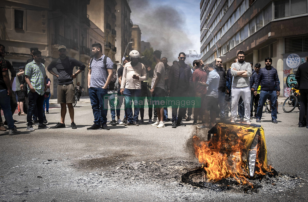 May 27, 2019 - Barcelona, Catalonia, Spain - Several backpacks of the company of Glovo are seen burning during the protest..Second day of protest of food on demand couriers service workers of the company Glovo, a Spanish start-up founded in Barcelona in 2015 operating in 24 countries. Glovo's freelance workers burned their backpacks for the second time in protest against the poor working conditions after a traffic accident death of a delivery partner who was hit on his bike by a municipal cleaning services truck. (Credit Image: © Paco Freire/SOPA Images via ZUMA Wire)