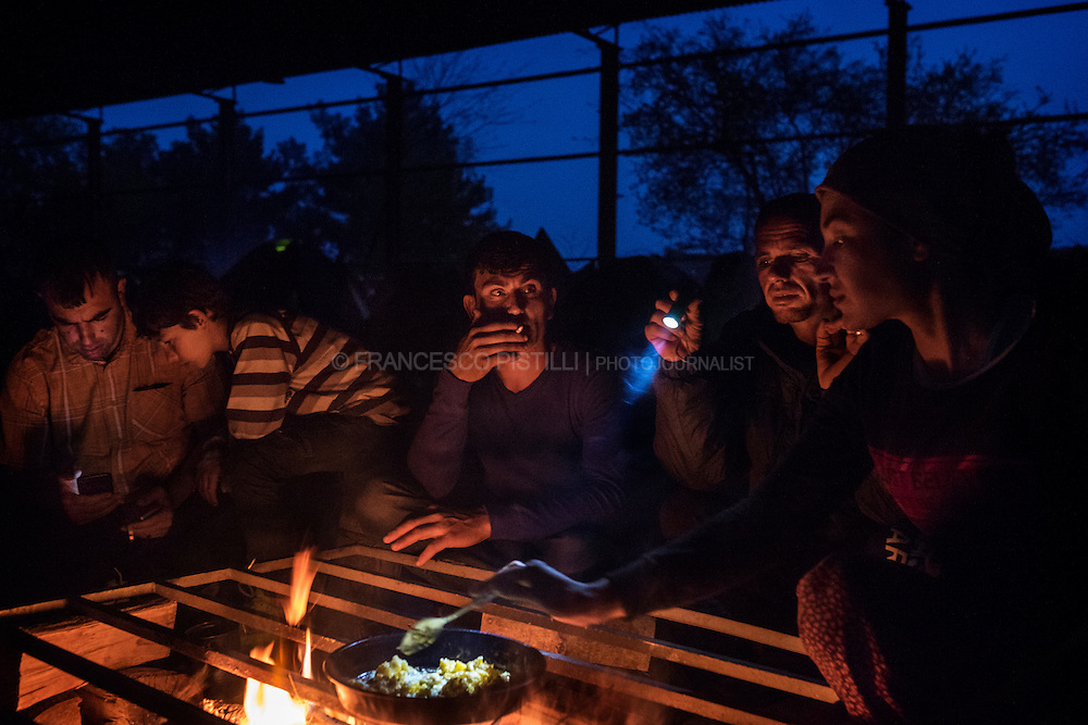 Kurdish families have dinner along the tracks in an abandoned hangar of Idomeni railway station near the Greek border with Macedonia.