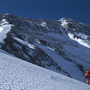 A climber ascends the North Ridge of Everest and gazes at the mighty North Face and Summit Pyramid rising above.