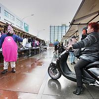 Nederland, Amsterdam , 20 oktober 2010..De kleding en stoffen afdeling van de markt op Plein 40-45.A market trader in the rain on the market on Plein 40-45 in Amsterdam.