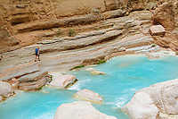 Young woman hiking up Havasu Creek while on a raft trip down the Grand Canyon National Park, AZ.