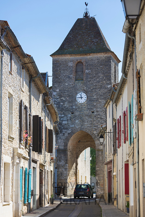 Small car passes through 13th Century medieval gateway clock tower in ancient bastide town Duras in Aquitaine, France