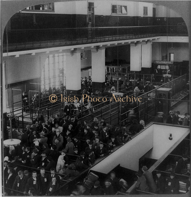 Immigrants just arrived in the USA from Europe waiting to be processed in the immigrant building, Ellis Island, New York.