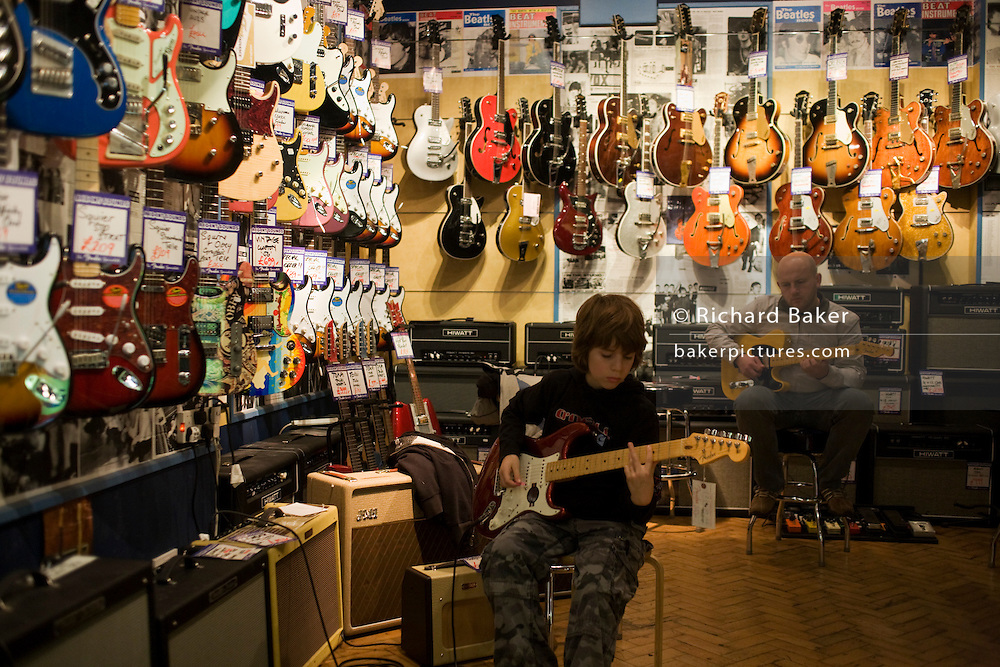 A 10 year-old boy and fellow-musician play amplified electric Fender guitars at Regent Sound at 4 Denmark Street, Tin Pan Alley