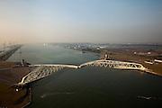 Nederland, Zuid-Holland, Nieuwe Waterweg, 19-09-2009; Functioneringssluiting Maeslantkering: de waterkering in de Nieuwe Waterweg wordt een maal per jaar, voordat het stormseizoen begint, getest. Tijdens  het sluiten van de kering ligt alle scheepvaartverkeer naar de Rotterdamse haven stil. Aan de horizon ingang van de Nieuwe Waterweg en Noordzee, links  Callandkanaal rechts Hoek van Holland.De Maeslantkering sluit normaal gesproken alleen bij dreigende stromvloed en bij een waterstand van 3 meter of meer boven NAP. De kering, onderdeel van de Deltawerken, vormt samen met de Hartelkering de Europoortkering en beschermt Rotterdam en achterland bij extreme waterstanden. .Netherlands, Hoek van Holland - Rotterdam harbour. Aerial view of the new storm surge barrier (Maeslantkering) in the Nieuwe waterweg during the so-called functioning closure, taking place one a year before the storm season begins. The waterway, leading to the Port of Rotterdam, is closed during the test.  At the horizon North Sea and tot the right Hook of Holland..luchtfoto (toeslag), aerial photo (additional fee required).foto/photo Siebe Swart
