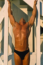 Man in a speedo stretching with his head back