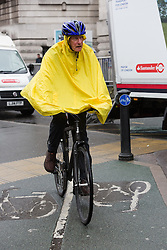 © Licensed to London News Pictures. 10/05/2016. LONDON, UK.  A cyclist in a rain poncho is caught in a heavy rain shower as he makes his way to work in central London this morning.  Photo credit: Vickie Flores/LNP