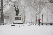 Red umbrella and the statue of Christopher Columbus in Central Park during a snow storm