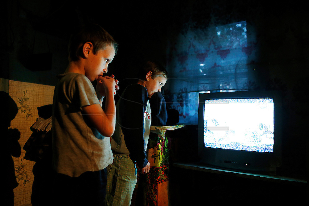 Bogdan and his brother Artem Shpak, 9 and 8 glaze as they watch tv.<br /> They live with their mother, their 2 brothers and their stepfather in a little house with poor living conditions. Last school vacations Bogdan went to Portugal and he will return next Summer.