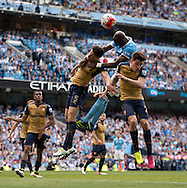 Eliaquim Mangala of Manchester City (2nd right) jumps for the ball with Hector Bellerin (right) and Gabriel Paulista of Arsenal during the Barclays Premier League match at the Etihad Stadium, Manchester<br /> Picture by Russell Hart/Focus Images Ltd 07791 688 420<br /> 08/05/2016