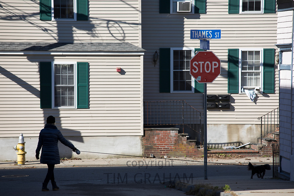 Woman walking past typical traditional painted wood clapboard houses in Thames Street, Newport, Rhode Island, USA