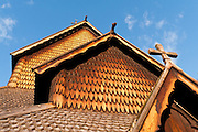 "Wood roof and siding detail. Heddal stave church is Norway's largest stave church. This triple nave stave church, which some call ""a Gothic cathedral in wood,"" was built in the early 13th century and restored in 1849-1851 and the 1950s. Heddal stavkirke is in Notodden municipality, Telemark County, Norway."