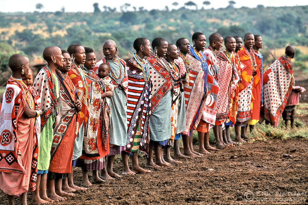 Maasai women perform a traditonal welcome including singing and dancing for tourists visiting their village (manyatta) in the Masai Mara in Kenya.
