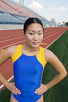 Female athlete smiling by running track, portrait