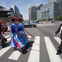 South Korea, Seoul,  Royal Guards in period military costume and carrying lances walk through crossalk along traffic circle toward Namdaemun Gate on spring morning