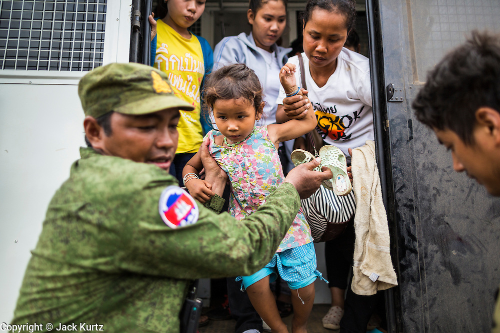16 JUNE 2014 - POIPET, CAMBODIA: A Cambodian soldier helps a child get out of a Thai immigration police truck in Poipet, Cambodia. More than 150,000 Cambodian migrant workers and their families have left Thailand since June 12. The exodus started when rumors circulated in the Cambodian migrant community that the Thai junta was going to crack down on undocumented workers. About 40,000 Cambodians were expected to return to Cambodia today. The mass exodus has stressed resources on both sides of the Thai/Cambodian border. The Cambodian town of Poipet has been over run with returning migrants. On the Thai side, in Aranyaprathet, the bus and train station has been flooded with Cambodians taking all of their possessions back to Cambodia.  PHOTO BY JACK KURTZ