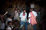 """Two guys are dancing in a house. A local custom is to ask, around the neighboring villages, food gift for the marriage's celebration, in which two child brides have just married with boys of 10 years largest. The legal age to get married in Ethiopia is 18, the law is quite often ignored. Education is the most important key to helping end the practice of forced child marriages. Many believe that education may prove to be more successful in preventing child marriages than banning child marriages..North West of Ethiopia, on saturday, Febrary 14 2009.....In a tangled mingling of tradition and culture, in the normal place of living, in a laid-back attitude. The background of Ethiopia's """"child brides"""", a country which has the distinction of having highest percentage in the practice of early marriages despite having a law that establishes 18 years as minimum age to get married. Celebrations that last days, their minds clouded by girls cups of tella and the unknown for the future. White bridal veil frame their faces expressive of small defenseless creatures, who at the age ranging from three to twelve years shall be given to young brides men adults already...To protect the identities of the recorded subjects names and specific places are fictional."""