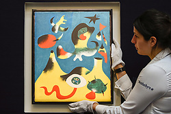 "© Licensed to London News Pictures. 14/06/2019. LONDON, UK. A technician presents ""Peinture (L'Air)"", 1938, by Joan Miró (Est. £10-15m). Preview of Impressionist and Modern art sales, which will take place at Sotheby's New Bond Street on 18 and 19 June 2019.   Photo credit: Stephen Chung/LNP"