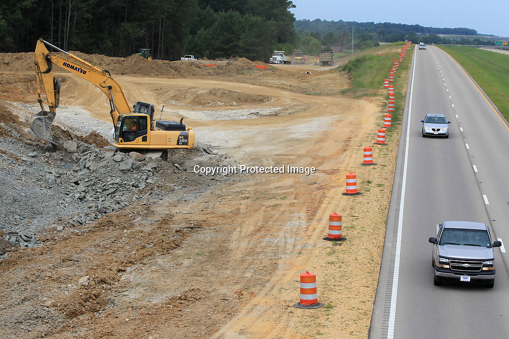 Traffic flows in the east bound lane as a worker in an excavator moves dirt at the crossing of South Thomas Street at Highway 76 as on and off ramps are being worked on by crews Tuesday morning in Tupelo.