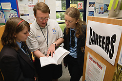 Careers advice teacher going through further education and options with secondary school pupils,