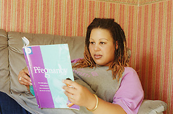 Pregnant young woman sitting on sofa reading information booklet about pregnancy,