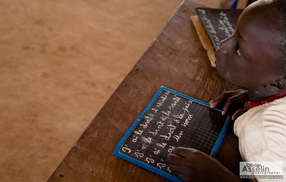 A girl writes the basic children's rights on her chalk board during class at the Kabiline I Primary school in the village of Kabiline, Senegal on Wednesday June 13, 2007.....