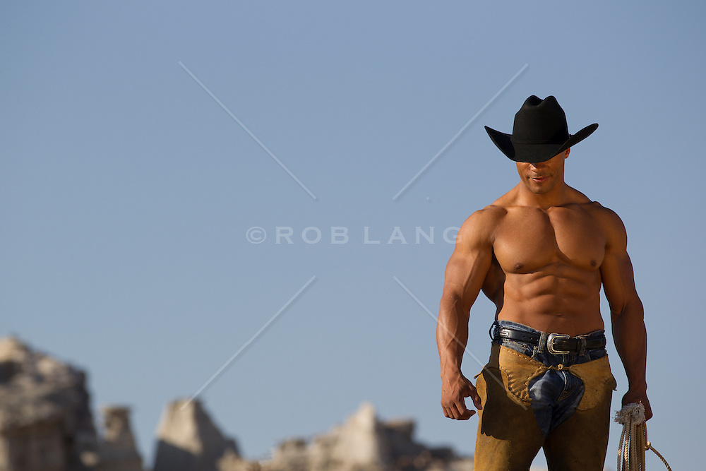 shirtless sexy African American cowboy with a great body walking through the Southwest landscape in Abiquiu