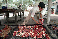 April 1986, Argentina --- A gaucho cook barbecues a side of lamb, steaks, and shish kebabs on a long grill in the ranch yard. Argentina. --- Image by © Owen Franken/