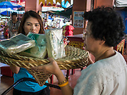 "10 AUGUST 2014 - BANGKOK, THAILAND:     Women pray with a basket of food staples they donated to the Poh Teck Tung Foundation on the first day of Ghost Month in Bangkok. The seventh month of the Chinese Lunar calendar is called ""Ghost Month"" during which ghosts and spirits, including those of the deceased ancestors, come out from the lower realm. It is common for Chinese people to make merit during the month by burning ""hell money"" and presenting food to the ghosts.  PHOTO BY JACK KURTZ"