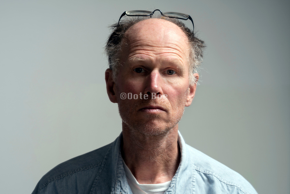 portrait of a 50+ years balding male person with glasses on top of his head